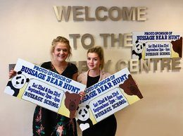 Jessica Pearce and Ellen Trueman, Sales Negotiators in The Property Centre's Stroud branch holding the Bussage Bear Hunt sold boards